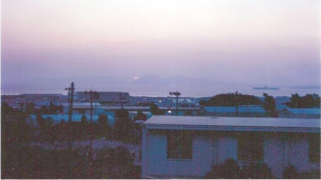 Athenai Air Base (1973)--taken from atop one of the barracks towards the flight line with the sun setting behind some of the Aegean Islands and a U.S. Navy ship (maybe one of the carriers) on the right