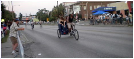 At dusk, before the start of the parade--surrey tram bikes carrying parade-goers around.