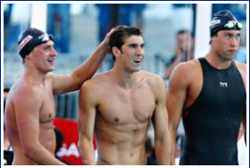 Ryan Lochte, Michael Phelps, and Matt Grevers watch as Nathan Adrian swims the final leg of the 4X100 relay.