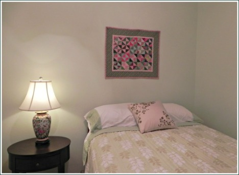 "Another ""project"" quilt made from Gai Perry's book hangs over the bed in the guest room."
