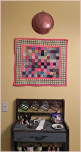 The first postage stamp quilt hangs above a stand full of my collected treasures and helps brighten the dining room.
