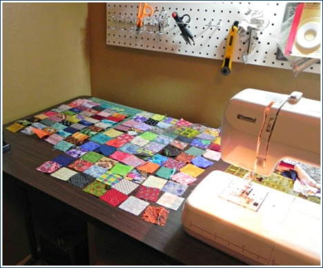 Several already pieced strips and a lot more blocks wait to be sewn together to make the top for a postage stamp quilt.