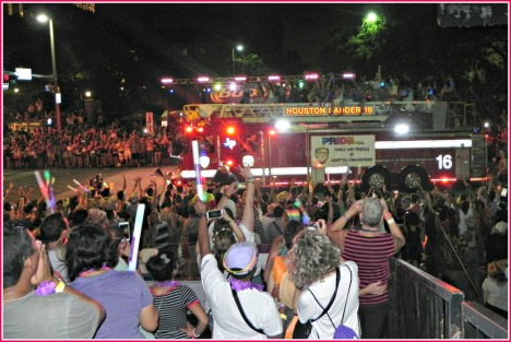 HFD's Ladder Truck 16 carries associated revelers on top as it makes it way down the Pride Houston Parade route.